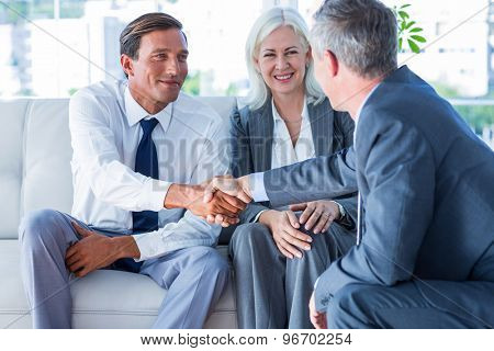 Business people shake hands on couch in office