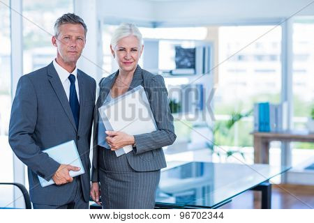 Happy business people looking at camera and holding shield in office