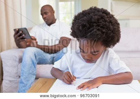 A little boy writing on notepad at home in living room
