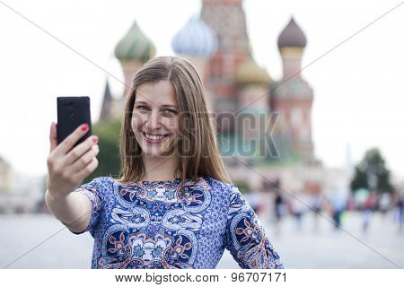 Selfie, Young beautiful girl photographed on a cell phone in red square, Moscow, Russia