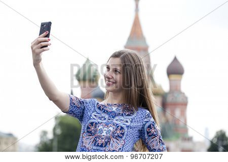 Selfie, Young beautiful girl photographed on a cell phone in a summer street