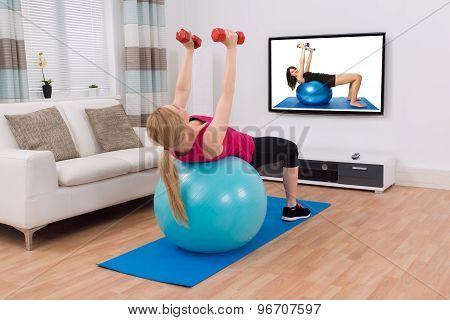 Woman Exercising With Fitness Ball And Dumbbell