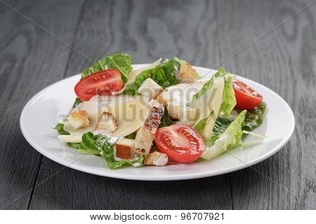 caesar salad with chicken on oak table