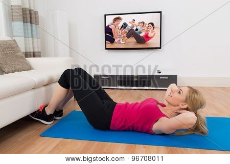 Woman Exercising In Front Of Television