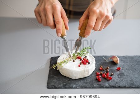 Woman's Hands Using Cheese Knife And Fork To Cut Camembert