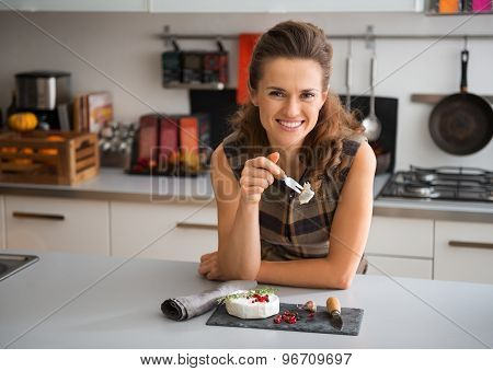 Smiling Woman Leaning On Counter Having Camembert Cheese