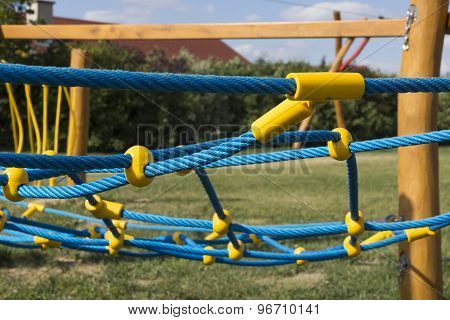 Yellow And Blue Rope-climbing Frame In The Playground