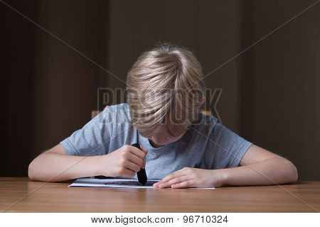 Boy Drawing With Black Crayon