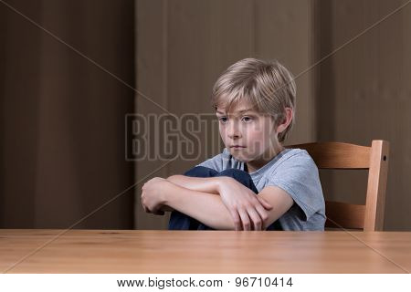 Unhappy Kid Sitting On Chair