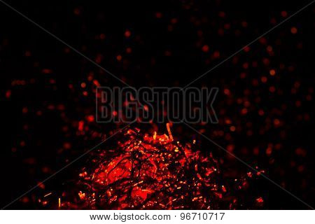 the dying fire and hot red sparks on a black background