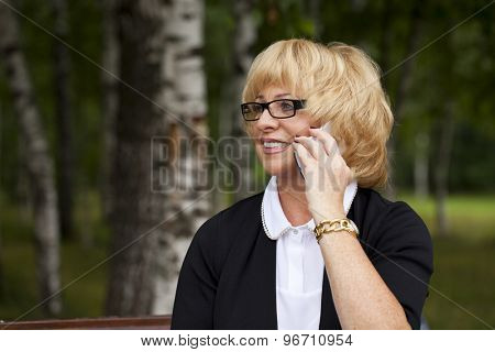 Elderly business woman in jacket sittin on bench with daily log, outdoor summer park