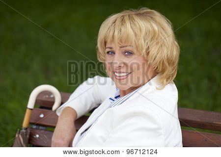 Elderly business woman in jacket sittin on bench, outdoor summer park