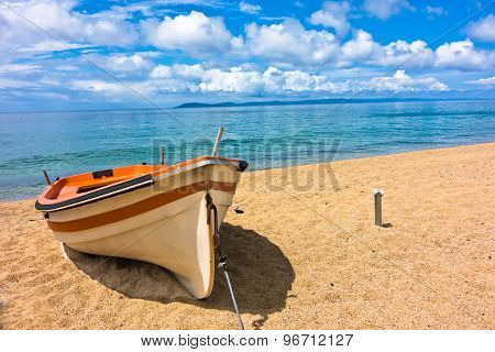 White boat on a sandy beach at morning, west coast of Sithonia