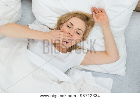 Woman Yawning In Bedroom