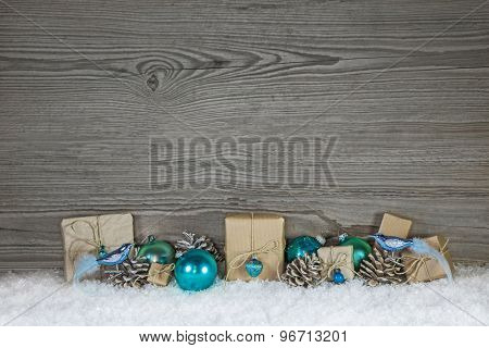 Grey wooden christmas background with turquoise decoration and gifts wrapped in paper.