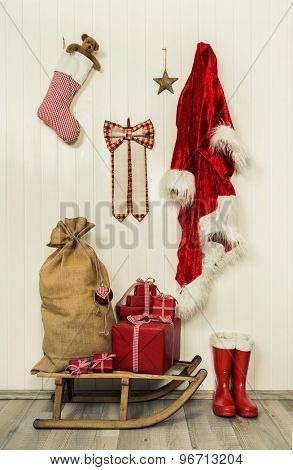 Santa utensils for a merry christmas with jacket, boots and presents in red and white colors.