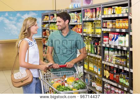 Smiling bright couple buying food products at supermarket