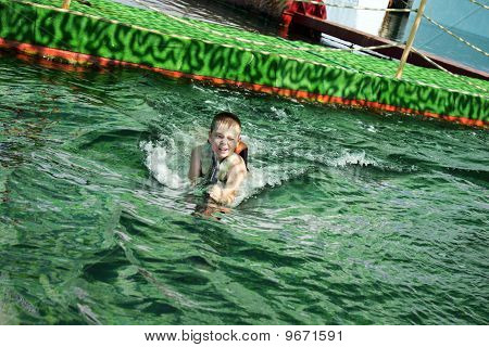 Squinting Boy Swimming With Dolphin