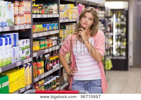 Portrait of a pretty blonde woman with finger next to mouth in supermarket