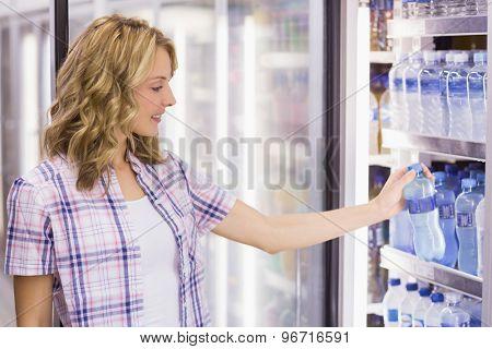 Smiling pretty blonde woman taking a water bottle in supermarket
