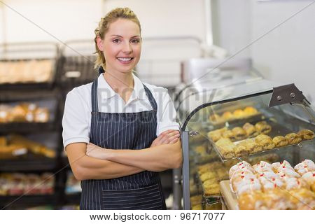 Portrait of a smiling blonde baker with arm crossed in bakery