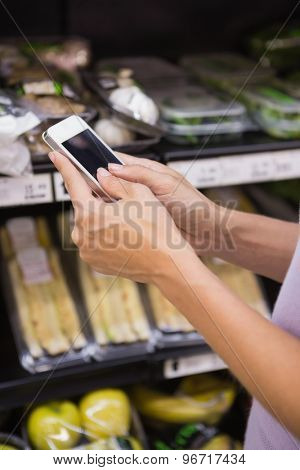 Close up view of a woman reading her shopping list on smartphone
