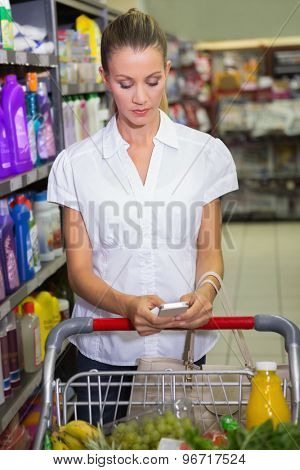 Woman buy products and texting at supermarket