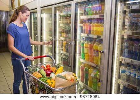 Pretty woman looking at camera and taking product on Pretty woman taking botlte of water in freezer at supermarket