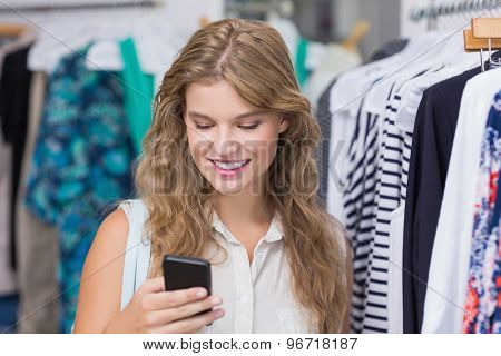A pretty blonde woman showing her credit cards in the clothing store