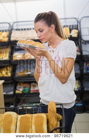 A woman smelling bread in the pastries shelf in the supermarket