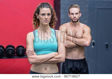 Muscular couple looking at the camera with woman ahead