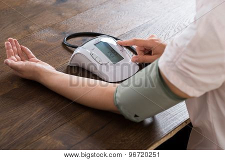 Close-up Of Businesswoman Measuring Blood Pressure