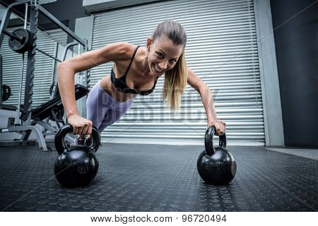 Portrait of muscular woman doing pushups with kettlebells