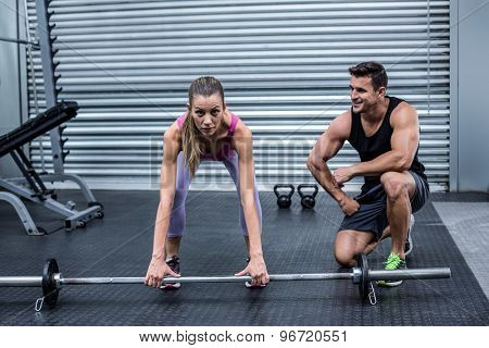 Attentive muscular woman lifting weight with her trainer behind