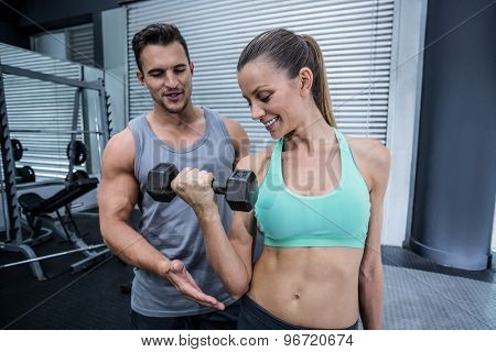 Trainer supervising a muscular woman lifting dumbbells