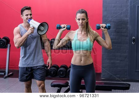 Trainer yelling through the megaphone while woman lifting dumbbells