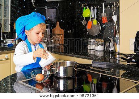 little boy cooking in kitchen interior