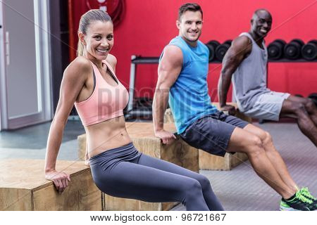 Portrait of three muscular athletes doing reverse push up