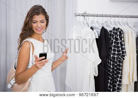 Smiling woman using smartphone at a boutique