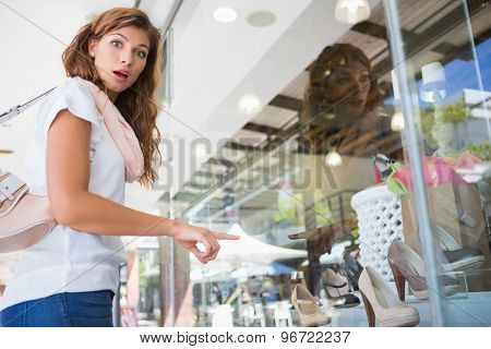 Portrait of surprised woman pointing the window at the shopping mall