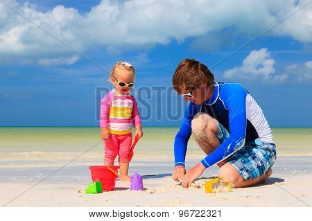 father and little daughter playing with sand on beach