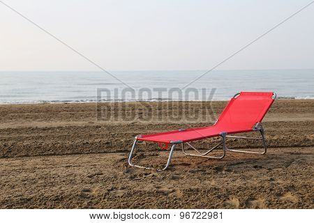 Red Sunlounger In The Middle Of The Beach In Summer On The Sea Shore