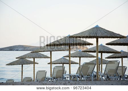 Parasol And Sunbeds At Sunset