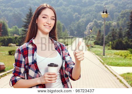 Pleasant young girl drinking coffee