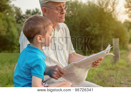 Senior man and child reading a newspaper outdoors