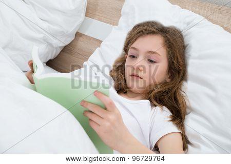 Girl Reading Book In Bedroom