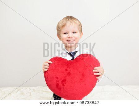 happy little boy holding heart