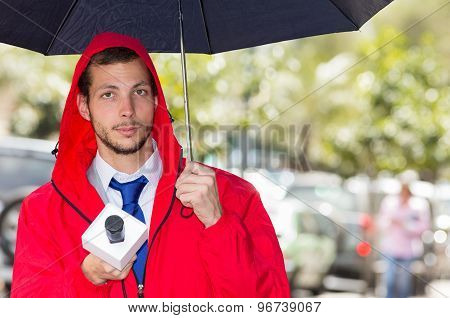Successful handsome male journalist wearing red rain jacket working in rainy weather outdoors park e