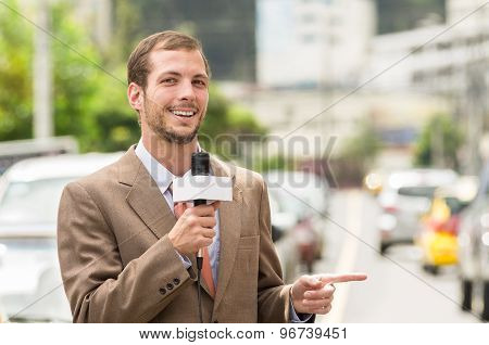 Successful attractive male journalist wearing brown suit working outdoors in traffic urban environme