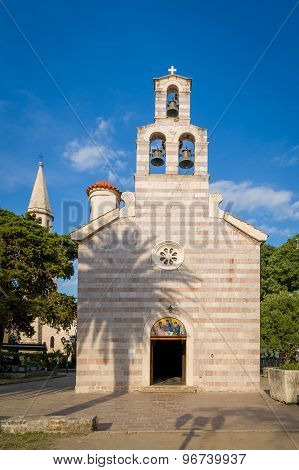 Old church with high bell tower in Budva